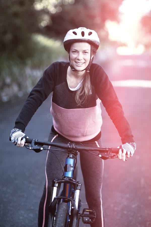 Portriat av den kvinnliga cyklisten med mountainbiket i bygd fotografering för bildbyråer