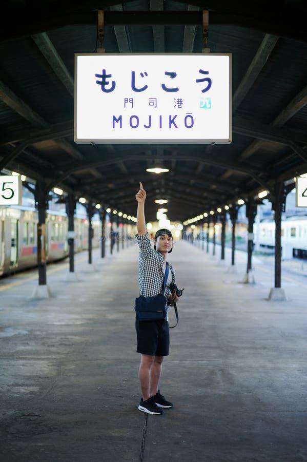 Portriat Azjatycki mężczyzna w przypadkowej odzieży punktach Szyldowy borad dworzec przy Mojiko, Japonia Japnases język znaczy Mo obraz royalty free