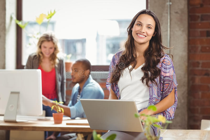 Portriat de la empresaria que usa el ordenador portátil en la oficina creativa imagenes de archivo