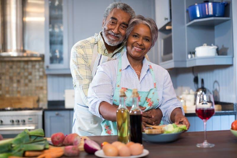 Portriat de los pares mayores sonrientes que preparan la comida imagen de archivo