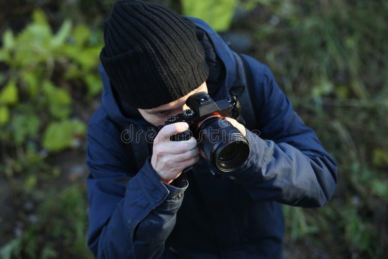 Portriat di giovane fotografo che fotografa all'aperto Equipaggi la presa foto con la macchina fotografica del dslr all'aperto fotografia stock libera da diritti
