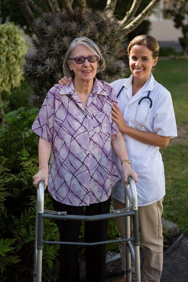Portriat di medico femminile che assiste donna nella camminata immagini stock libere da diritti