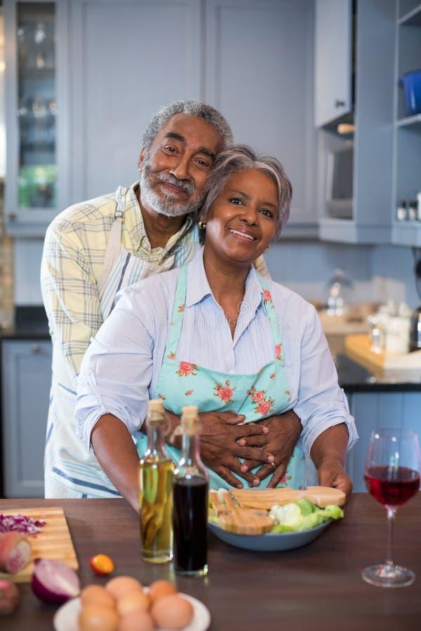 Portriat dos pares superiores de sorriso que preparam o alimento fotos de stock royalty free