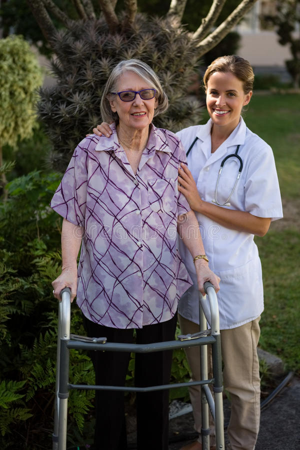 Portriat of female doctor assisting woman in walking. Portriat of female doctor assisting women in walking at yard royalty free stock images