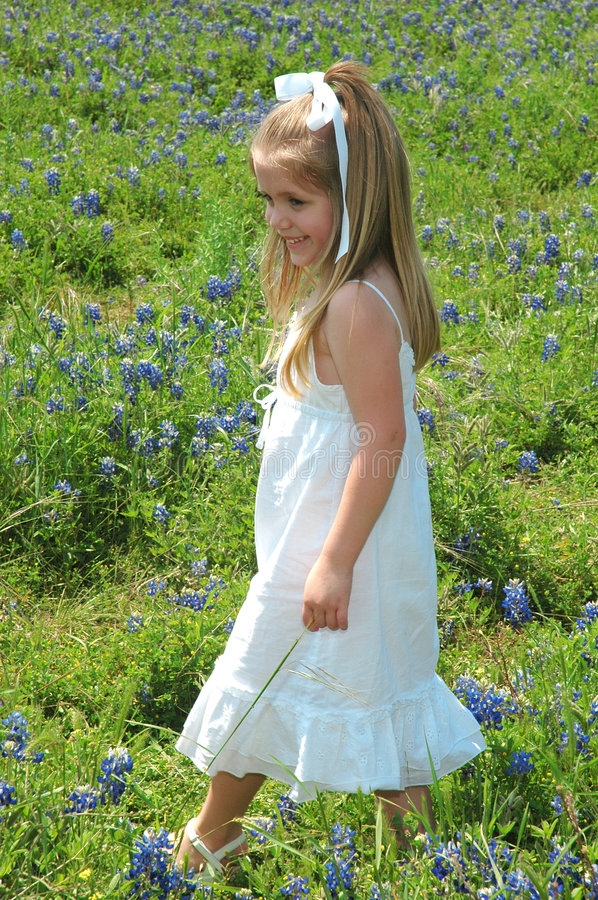 Portriat in Flowers. Beautiful girl walking threw flowers. Blue Bonnets are native Texas flowers. The Blue Bonnet is the State Flower of Texas, USA royalty free stock photo