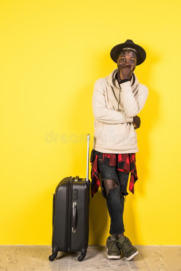 Portriat of young african happy man holding passport and suitcase standing isolated over yellow background royalty free stock photography