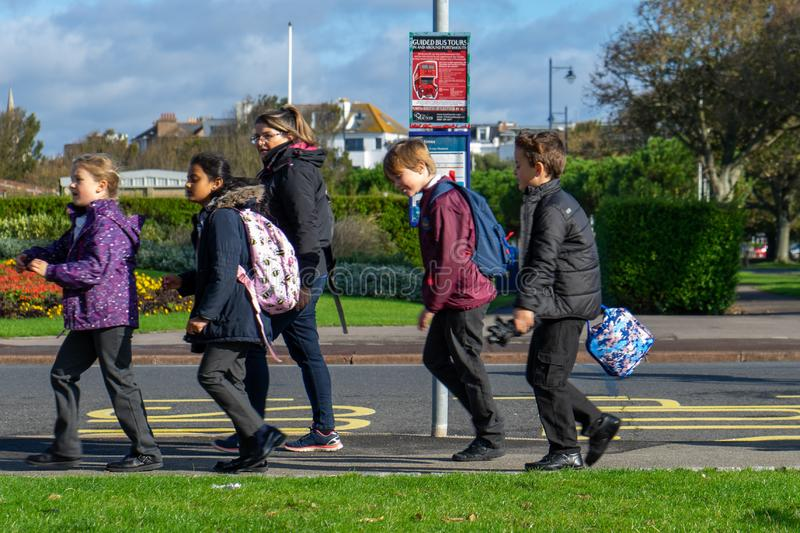 A group of British school children walking past a bus stop. 10/09/2019 Portsmouth, Hampshire, UK A group of British school children walking past a bus stop stock photos