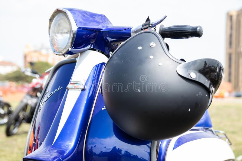 A motorbike helmet on the handlebars of a vintage scooter or moped stock images
