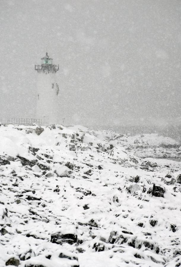 New England Lighthouse Flashes green During Snowstorm. Portsmouth lighthouse, also known as Fort Constitution light, shines a green light during a New England royalty free stock image