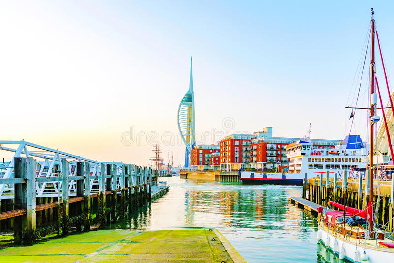 Portsmouth Spinaker tower with harbour. PORTSMOUTH, UNITED KINGDOM - JUNE 06: Portsmouth Emirates Spinaker tower in the distance with shipping harbor at sunset stock image