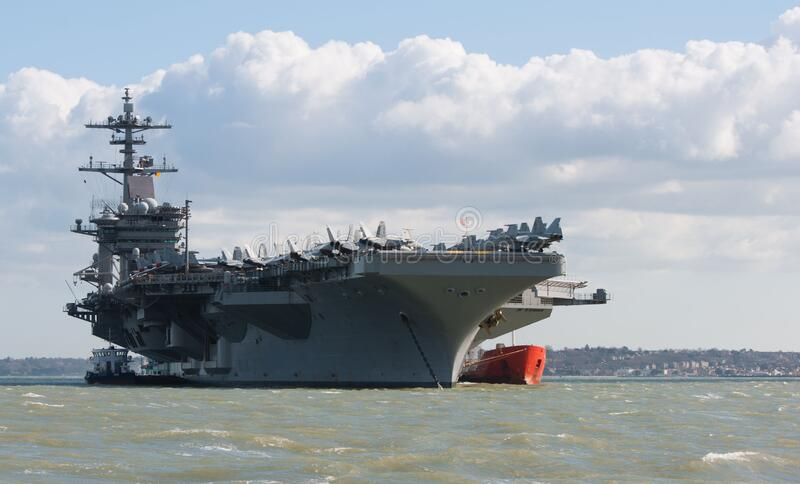Portsmouth, United Kingdom - March 26, 2015: USS Theodore Roosevelt anchored in the Solent off Portsmouth on its five day visit to. The USS Theodore Roosevelt royalty free stock images