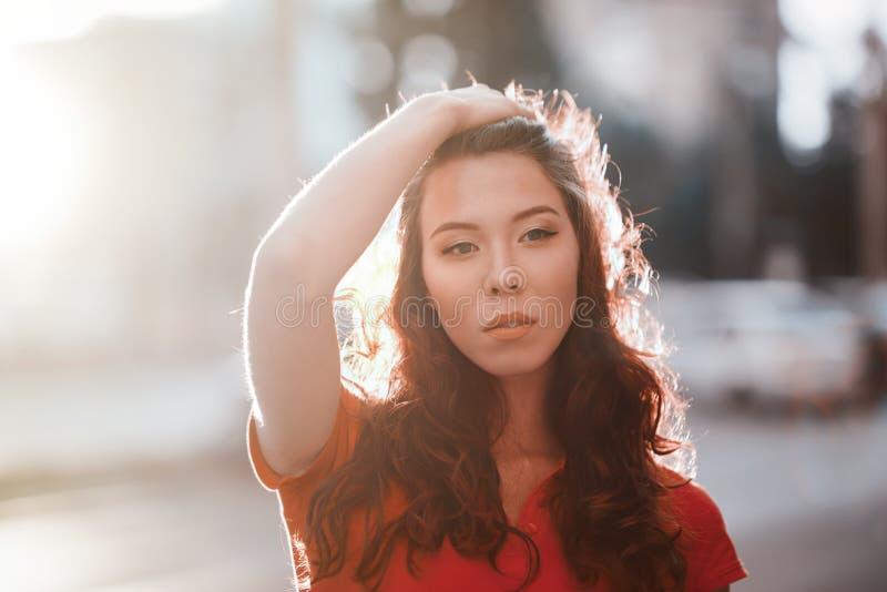 Porttrait al aire libre del verano de la muchacha bonita joven que presenta en la puesta del sol en ciudad imágenes de archivo libres de regalías
