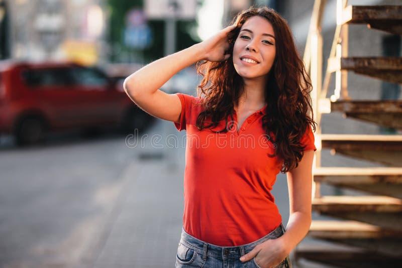 Porttrait al aire libre del verano de la muchacha bonita joven que presenta en la puesta del sol en ciudad imagen de archivo