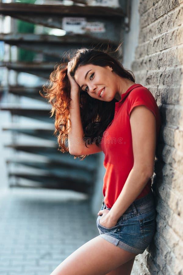 Porttrait al aire libre del verano de la muchacha bonita joven que presenta en la puesta del sol en ciudad foto de archivo libre de regalías
