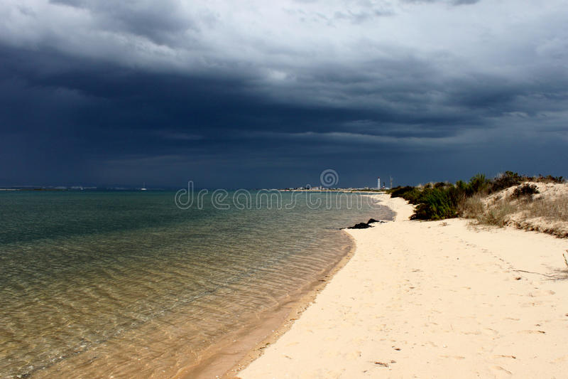 Portugal. Algarve. Ilha deserta. Sand and ocean before storm on dark blue sky background, horizontal view. Portugal. Algarve. Ilha deserta. Sand and ocean stock photos