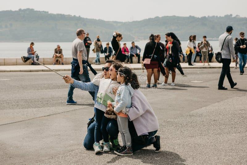 Portugal, Lisboa, o 1º de maio de 2018: Um pai asiático novo da família, a mãe e duas filhas fazem um selfie emocional no fotos de stock royalty free