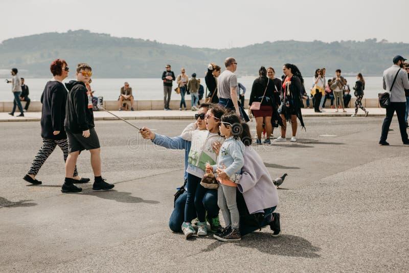 Portugal, Lisboa, o 1º de maio de 2018: Um pai asiático novo da família, a mãe e duas filhas fazem um selfie emocional no imagens de stock