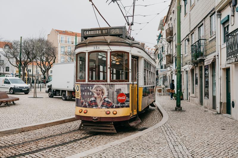Portugal, Lisbon, 01 July 2018: An old-fashioned vintage traditional yellow tram moving along the city street of Lisbon stock images