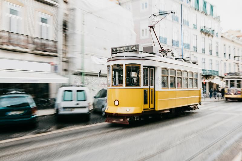 Portugal, Lisbon, 01 July 2018: An old-fashioned vintage traditional yellow tram moving along the city street of Lisbon stock photos