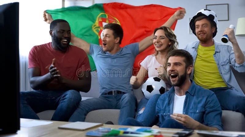 Portugal multi-étnico ventila a observação do fósforo em casa, comemorando o objetivo junto imagens de stock royalty free