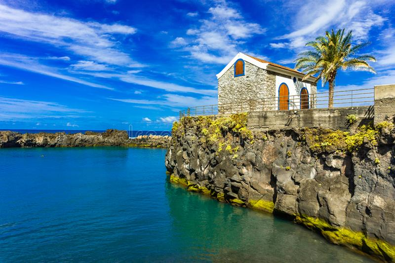 Portugal small old house, tranquil surface of the ocean, coast of Madeira island stock photography
