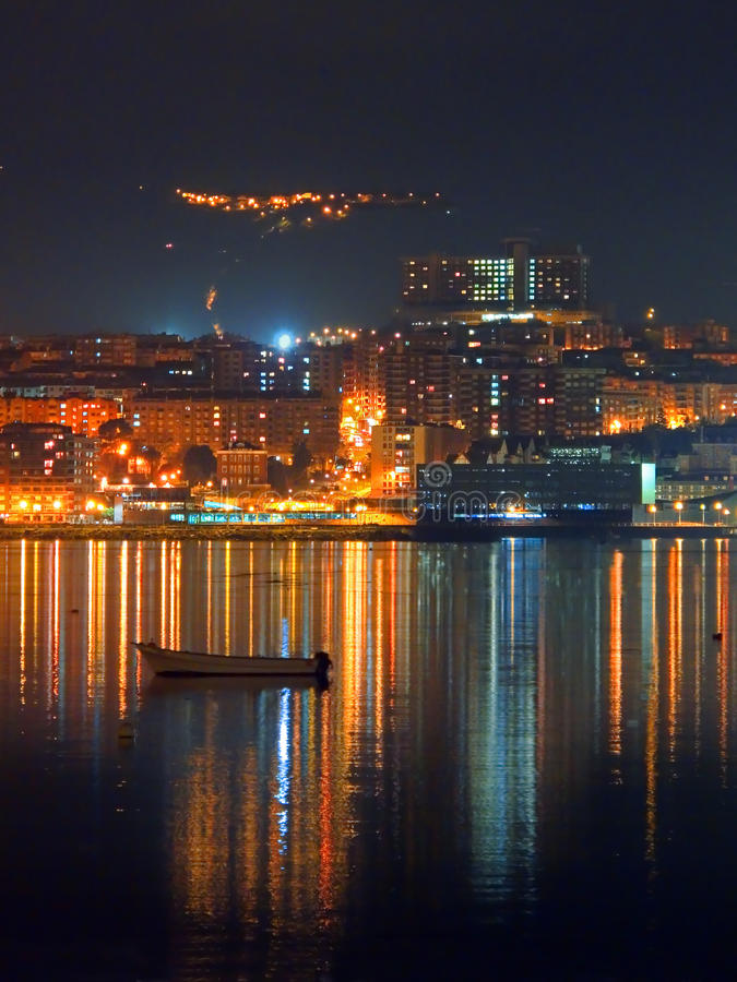 Portugalete alla notte con le luci e le riflessioni della città fotografia stock libera da diritti