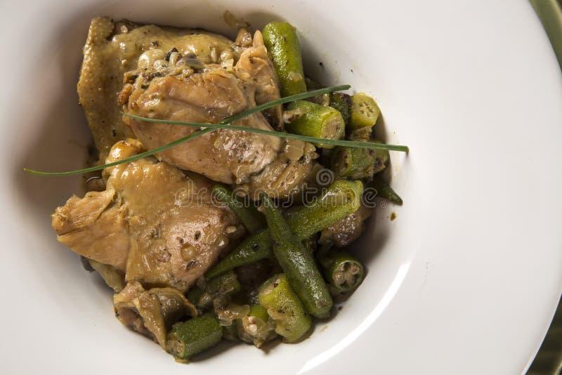 Portugis för Frango com-quiabo för `-höna med okra`, brasiliansk maträtt i den vita plattan arkivfoto