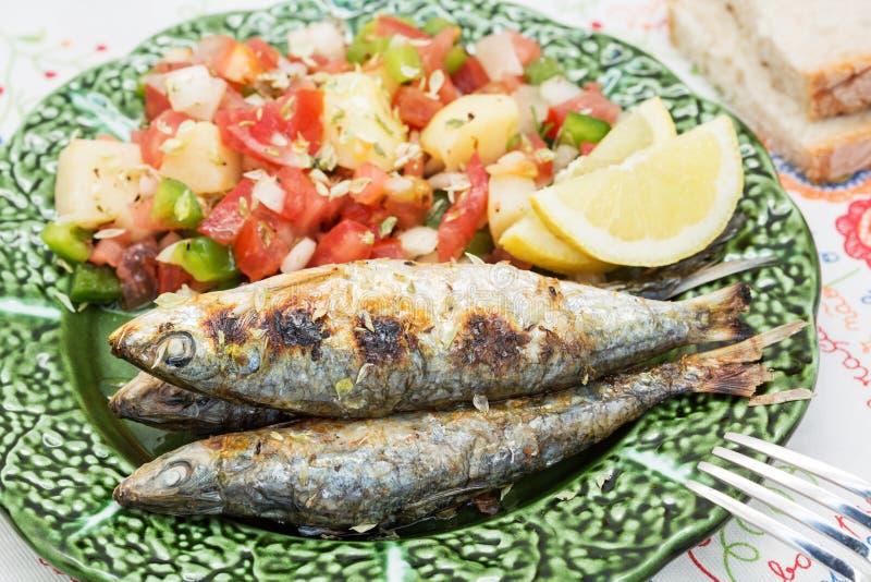 Portugisisk stil grillade sardiner med sallad arkivfoton