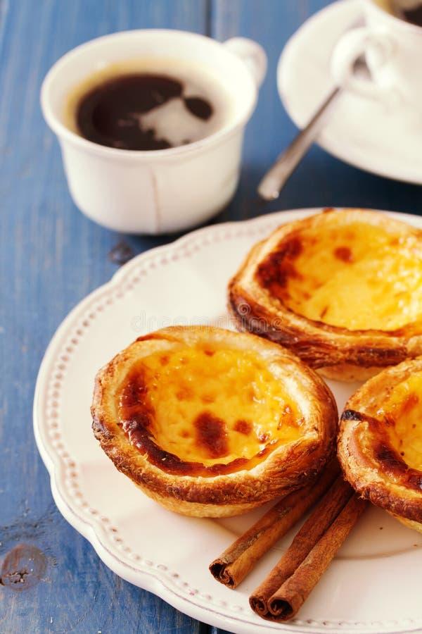 Portugisiska kakor med kanel på den vita maträtten med koppen kaffe arkivbilder