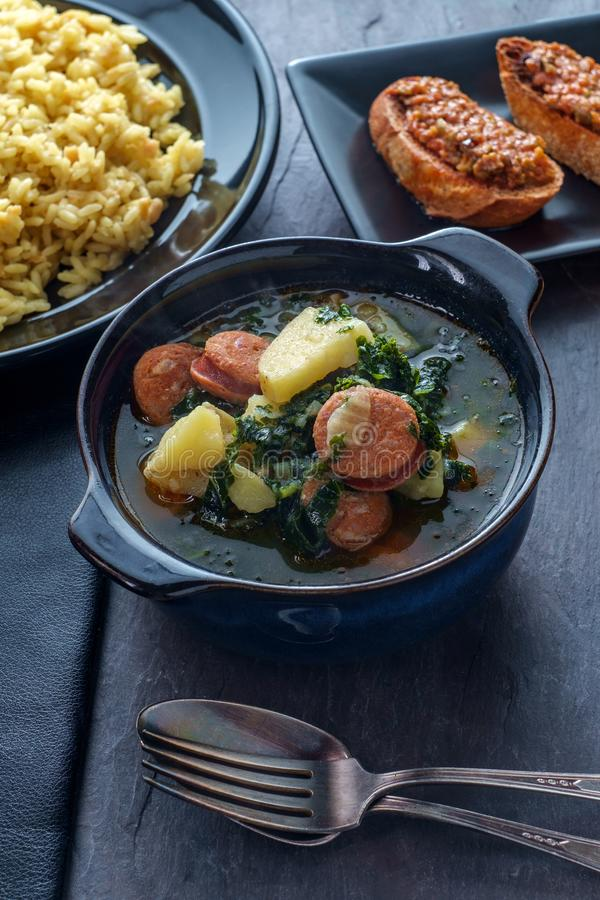 Portuguese Caldo Verde Soup. Traditional Portuguese caldo verde chourico soup with orzo rice pilaf and petiscos stock photography