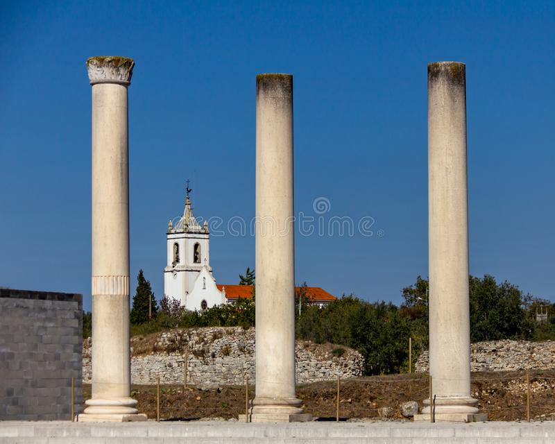 Portuguese church and roman ruins. Church framed by Roman Columns at Conimbriga in Portugal under a cloudless blue sky stock photos