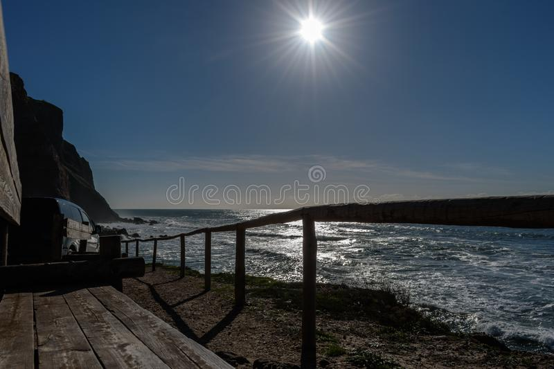 Wooden benches and fence with car parked next to cliff on Porto Barril beach with bright sun, Ericeira - Mafra, Portugal stock photos