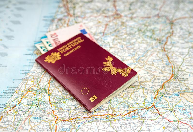 The Portuguese passport and euro banknotes on a geographical map royalty free stock photos