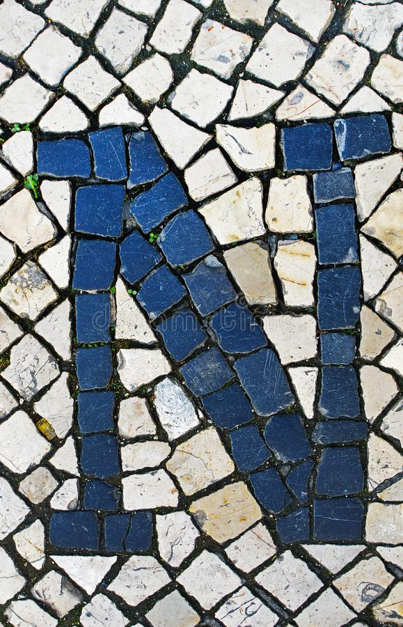 Portuguese sidewalk of calcada in the form of the letter D. Lisb. Portuguese sidewalk of calcada in the form of the letter N. Lisbon, Portugal stock photography