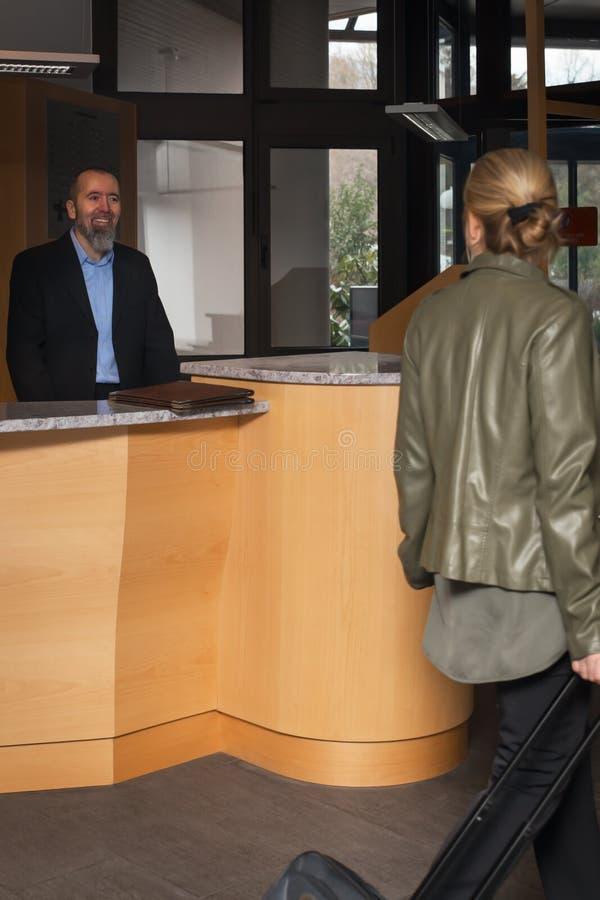 Portvakten i ett hotell smilling till en kvinnlig gäst arkivfoto