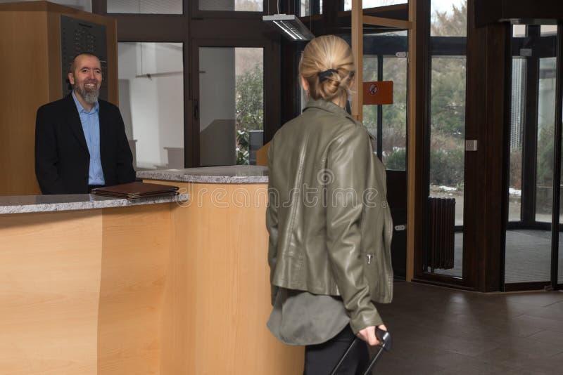 Portvakten i ett hotell smilling till en kvinnlig gäst royaltyfri foto
