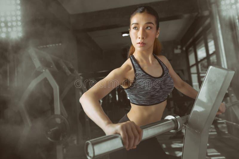 Portyvrouw die met barbell in gymnastiek uitoefenen stock afbeelding