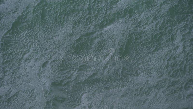 Poruszające wodne tekstury jak fale dosięgają brzeg zdjęcie stock