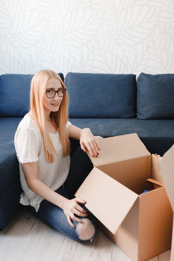 Poruszający dom: Młodej kobiety chodzenie w nowych mieszkania mienia kartony z należeniami, blondynki dziewczyny sittng blisko ka obrazy stock