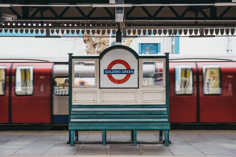 Poruszający pociąg za stacyjnym imię znakiem na plenerowej platformie Golders zieleni stacja metra, Londyn, UK obraz royalty free