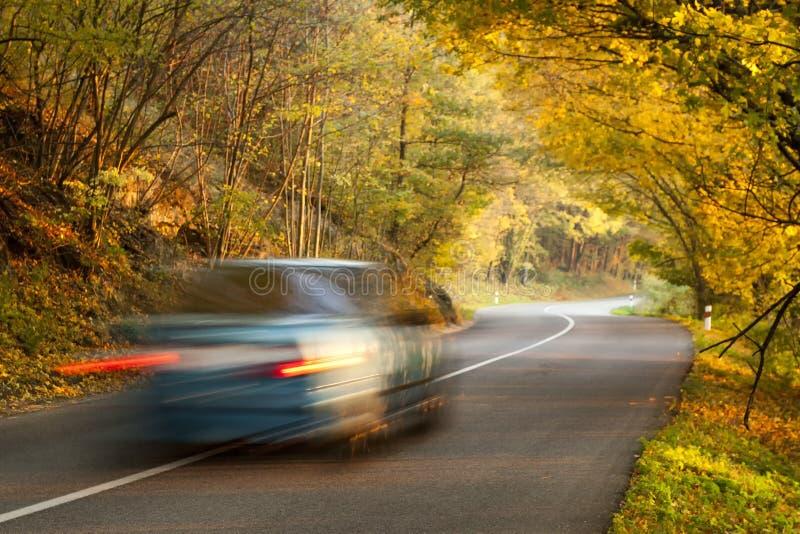 Poruszający samochód na drodze w jesień naturze obraz stock