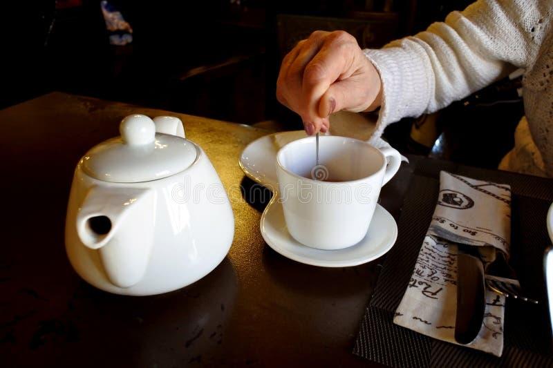 Porywający cukier z teaspoon w kubku gorąca herbata zdjęcia stock