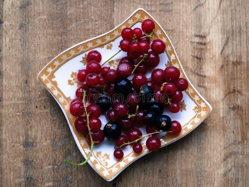 Porzeczkowe jagody na talerzu na drewnianym stole obraz stock