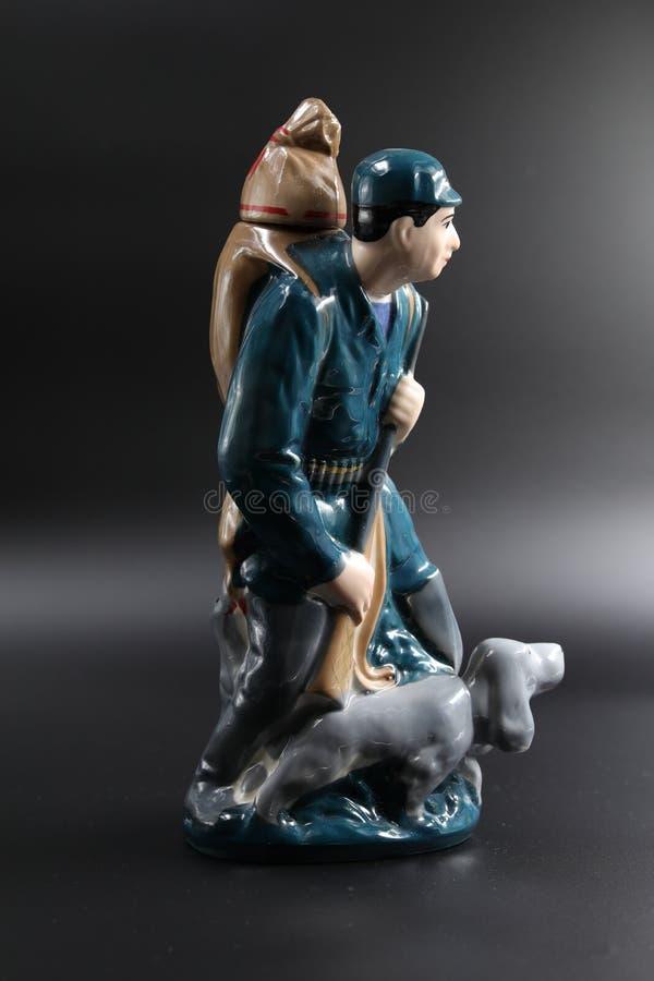 Porzellanfigur des Jägers mit einem Hund gegen einen dunklen Hintergrund, abhängiges Schießen lizenzfreie stockfotografie