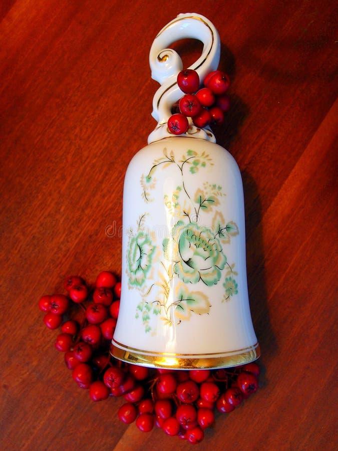 Porzellanglocke mit roten Weihnachtsbeeren lizenzfreie stockbilder