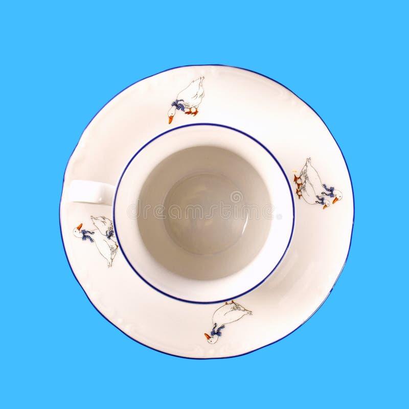 Porzellanschale mit einer Untertasse auf blauem Hintergrund stockbild