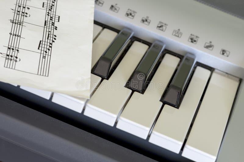 Porzion del teclado y de la partitura musical electrónicos imagenes de archivo
