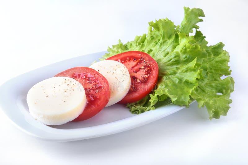 Porzione di mozzarella con i pomodori, la foglia della lattuga ed il condimento balsamico sul piatto bianco colpo del primo piano immagine stock libera da diritti