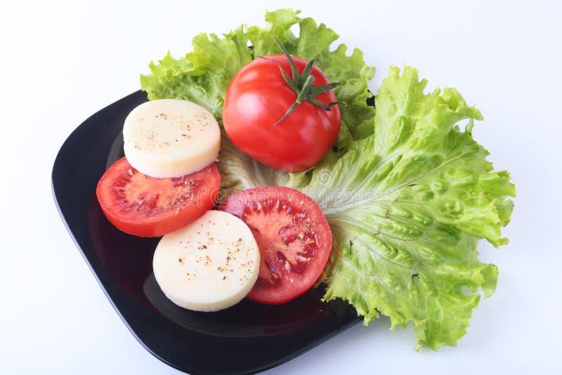 Porzione di mozzarella con i pomodori, la foglia della lattuga ed il condimento balsamico sulla banda nera colpo del primo piano  fotografie stock