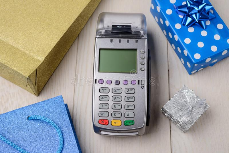 POS terminal between gift boxes. And pockets on white wooden background. Paying for Christmas presents stock photography